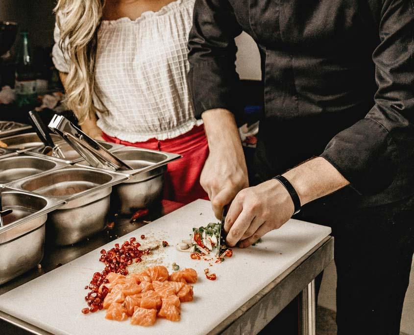 Küchenchef zeigt Kollegin das Schneiden von Zutaten