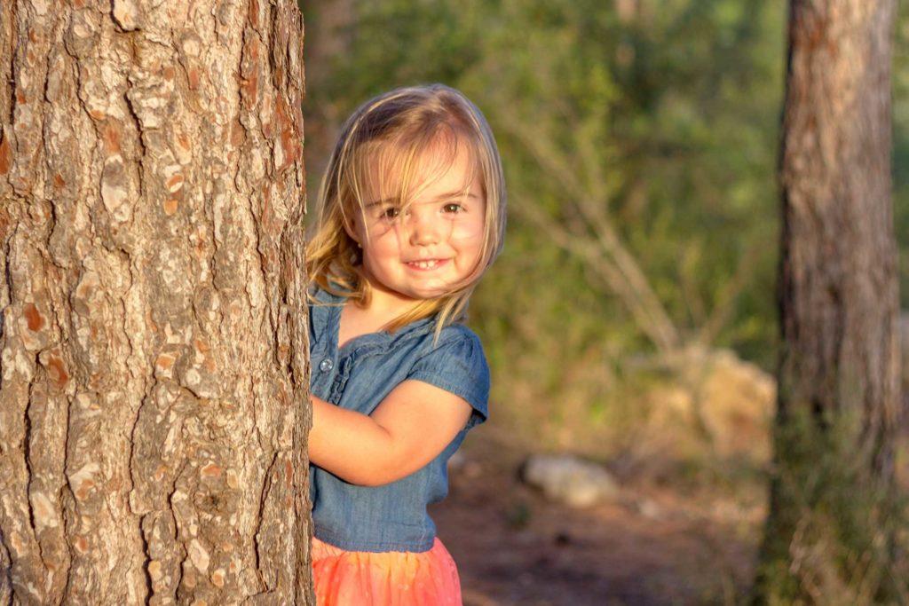 süßes Mädchen umarmt Baum